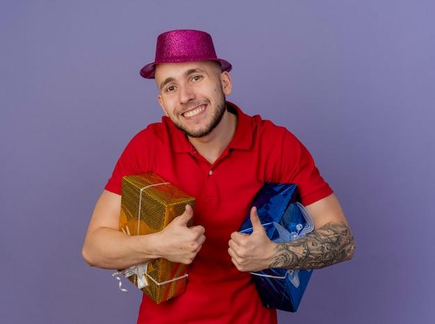 Szczęśliwy młody przystojny facet słowiańskich partii sobie kapelusz strony gospodarstwa pakiety prezentów patrząc na kamery na białym tle na fioletowym tle