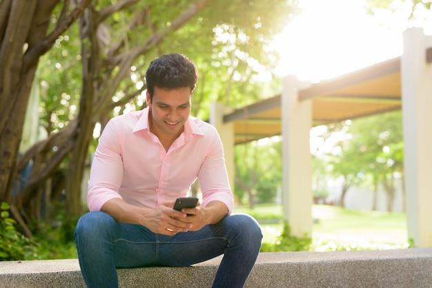Szczęśliwy młody przystojny indyjski biznesmen przy użyciu telefonu i siedząc w parku