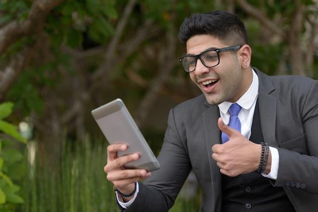 Szczęśliwy młody przystojny indyjski biznesmen rozmowy wideo z cyfrowego tabletu w parku