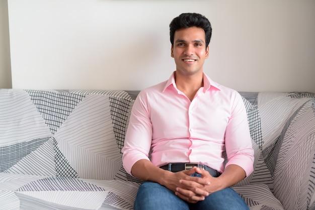 Szczęśliwy młody przystojny indyjski biznesmen, uśmiechając się w salonie w domu