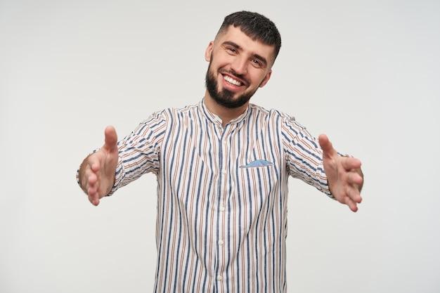 Szczęśliwy młody przystojny krótkowłosy brunet brodaty facet w pasiastej koszuli patrząc wesoło z szerokim uśmiechem, stojąc nad białą ścianą z otwartymi ramionami
