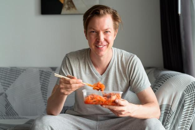 Szczęśliwy młody przystojny mężczyzna jedzenie kimchi w salonie w domu
