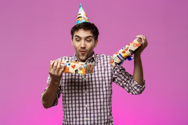 Szczęśliwy młody przystojny mężczyzna otwiera prezent urodzinowy nad purpury ścianą.