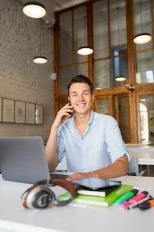 Szczęśliwy młody przystojny mężczyzna siedzi w biurze