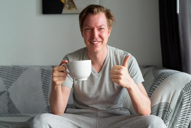 Szczęśliwy młody przystojny mężczyzna trzyma filiżankę kawy i daje kciuki do góry w domu