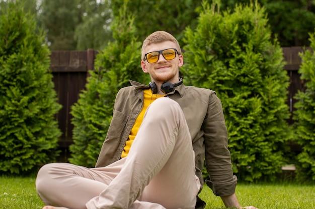 Szczęśliwy młody przystojny mężczyzna w słuchawkach odpoczywa, siedząc na trawie na zewnątrz, muzyczne radio podcast edukacyjny, lato zielony charakter. motywacja nastrój playlista, rozrywka, koncepcja dźwięków harmonii