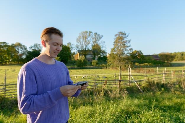 Szczęśliwy młody przystojny mężczyzna za pomocą telefonu komórkowego w spokojnej trawiastej równinie z naturą
