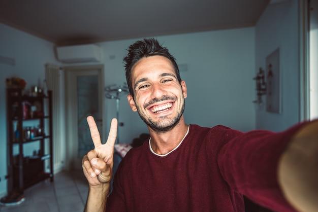Szczęśliwy młody przystojny millenials robienia selfie, uśmiechając się do kamery w salonie w domu.