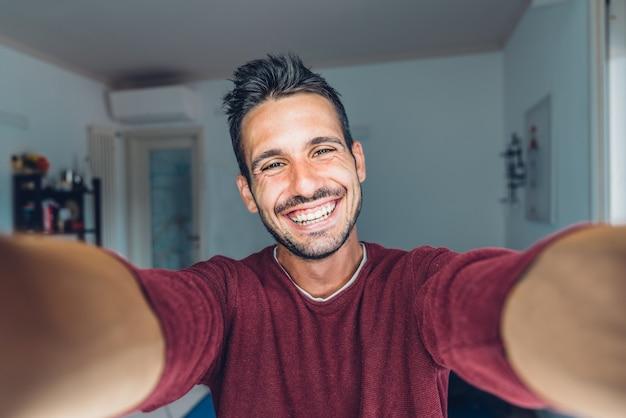 Szczęśliwy młody przystojny millenials robienia selfie uśmiechnięty w salonie w domu.