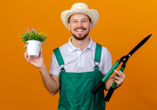 Szczęśliwy młody przystojny ogrodnik słowiański w mundurze i kapeluszu, trzymając kwiat i sekatory, patrząc na białym tle
