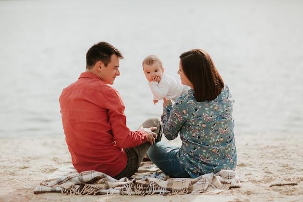 Szczęśliwy młody rodzinny obsiadanie blisko wody.