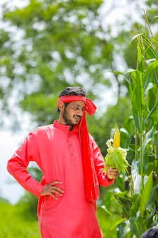 Szczęśliwy młody rolnik indyjski pokazano owoce kukurydzy w polu