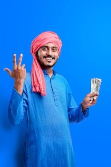 Szczęśliwy młody rolnik indyjski pozowanie z walutą na niebieskim tle.
