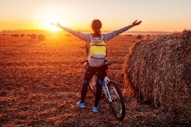 Szczęśliwy młody rowerzysta podnosząc otwarte ramiona w jesiennym polu podziwiając widok. kobieta bogata w cel. darmowa energia