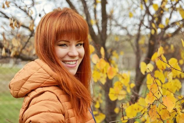 Szczęśliwy młody rudy dziewczyna portret na zewnątrz jesienią