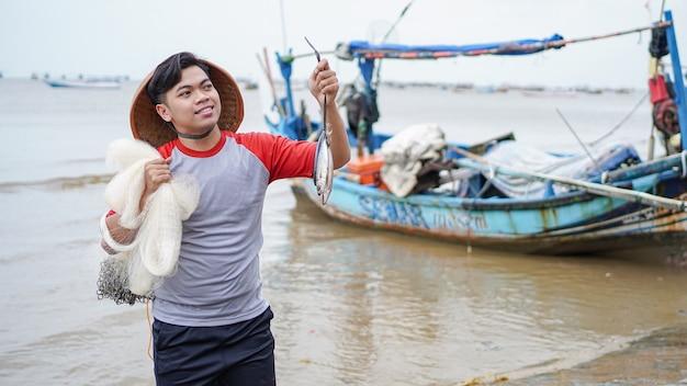 Szczęśliwy młody rybak na plaży, trzymając swój połów ryb i pokazuje przed swoją łodzią