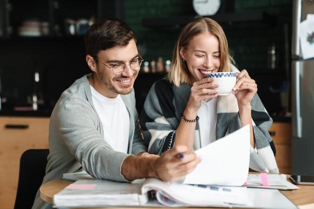 Szczęśliwy młody, rzeczowy mężczyzna i kobieta razem robią obliczenia i papierkową robotę w kawiarni