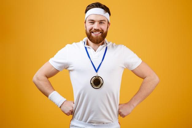 Szczęśliwy młody sportowiec patrzeje kamerę z medalem.