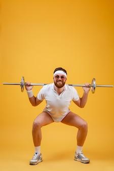 Szczęśliwy młody sportowiec robić ćwiczenia sportowe ze sztangą