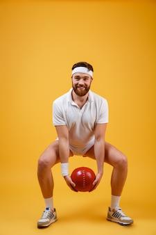 Szczęśliwy młody sportowiec trzyma piłkę wykonuje ćwiczenia sportowe.
