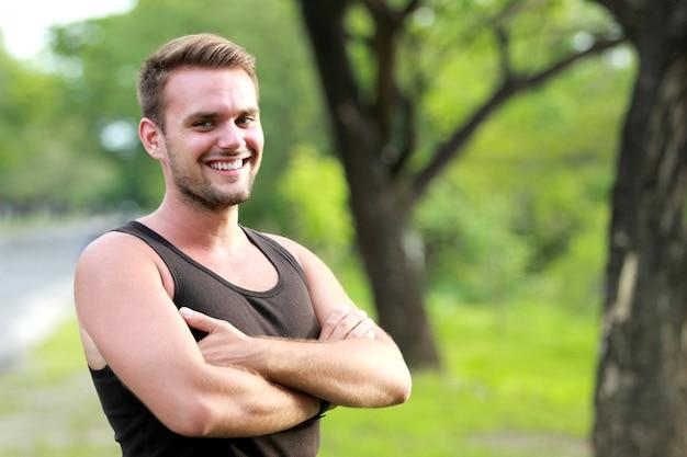 Szczęśliwy młody sportowiec uśmiechnięty i poza z założonym ramieniem