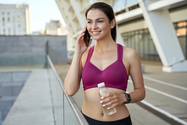 Szczęśliwy młody sportowiec używający telefonu komórkowego na zewnątrz