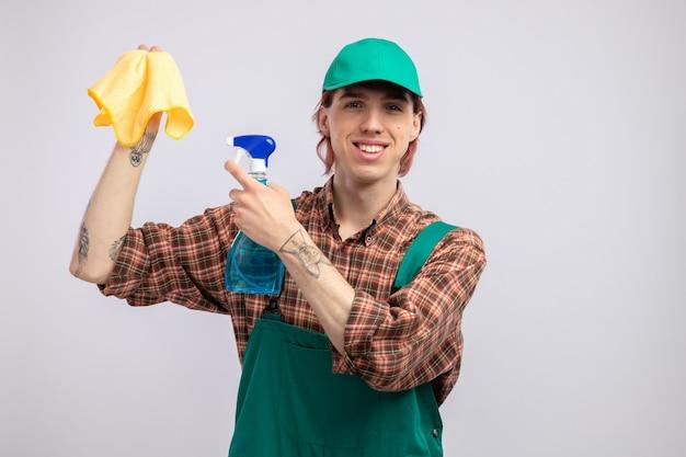 Szczęśliwy młody sprzątacz w kombinezonie koszulowym w kratę i czapce, trzymając szmatkę i spray do czyszczenia wskazując palcem wskazującym na szmatę, uśmiechając się radośnie stojąc nad białą ścianą