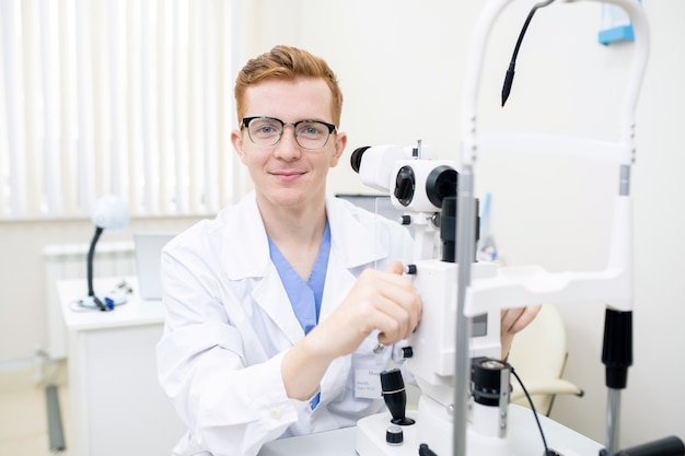 Szczęśliwy młody stażysta w białym fartuchu i okularach patrzy na ciebie podczas używania nowego sprzętu okulistycznego