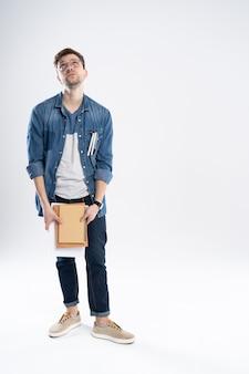 Szczęśliwy młody student stojący pełnej długości z książkami i notatkami na białym tle.