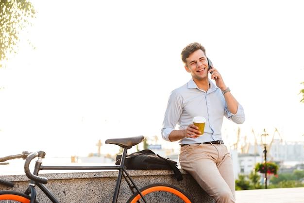 Szczęśliwy młody stylowy mężczyzna rozmawia przez telefon komórkowy