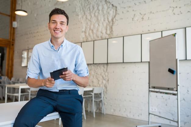 Szczęśliwy młody stylowy uśmiechnięty mężczyzna w biurze co-working, startowy freelancer trzymając za pomocą tabletu