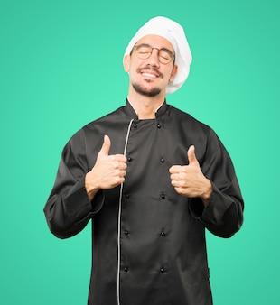 Szczęśliwy młody szef kuchni gestem, że wszystko jest w porządku
