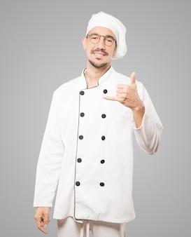 Szczęśliwy młody szef kuchni robi gestowi dzwonić z ręką