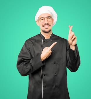 Szczęśliwy młody szef kuchni robi skrzyżowanym palca gestowi