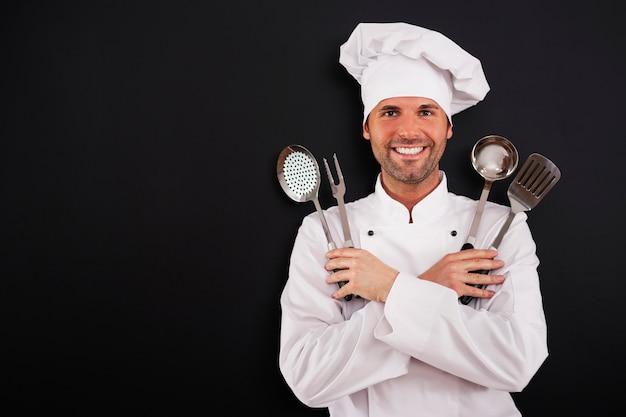 Szczęśliwy młody szef kuchni ze sprzętem do gotowania