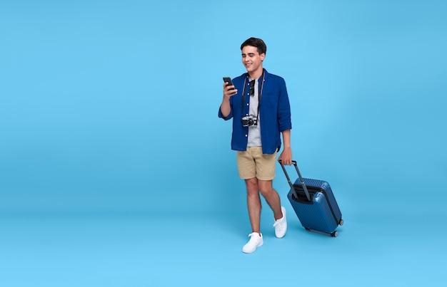 Szczęśliwy młody turysta azjatycki mężczyzna trzyma smartfon z bagażem będzie podróżować na wakacje na niebieskim tle.