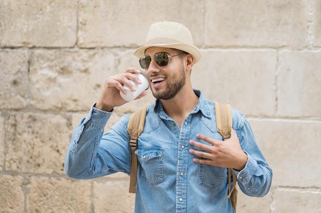 Szczęśliwy młody turysta z kawą na wynos i plecakiem chodzącym po ulicy