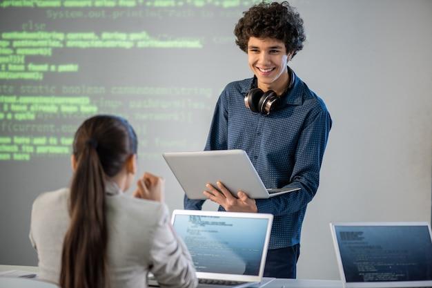 Szczęśliwy młody uczeń z laptopem patrząc na swojego kolegę z klasy siedzącego przed nim podczas dyskusji lub konsultacji na lekcji