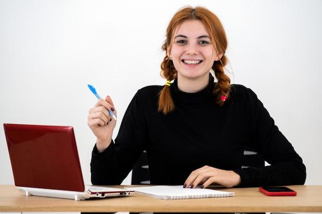 Szczęśliwy młody urzędnik kobiety obsiadanie za pracującym biurkiem z laptopem