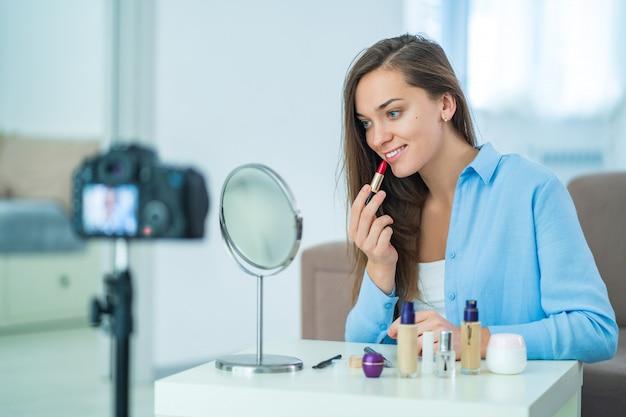 Szczęśliwy młody uśmiechnięty kobiety blogger używa czerwoną pomadkę dla maluje wargi podczas nagrywać jej piękno blog o makijażu i kosmetykach w domu. blogowanie i niezależni ludzie
