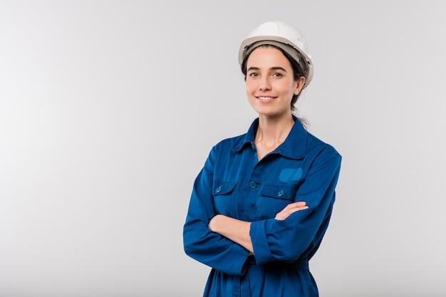 Szczęśliwy młody uzbrojony kobieta inżynier w niebieskiej odzieży roboczej i kasku stoi w izolacji