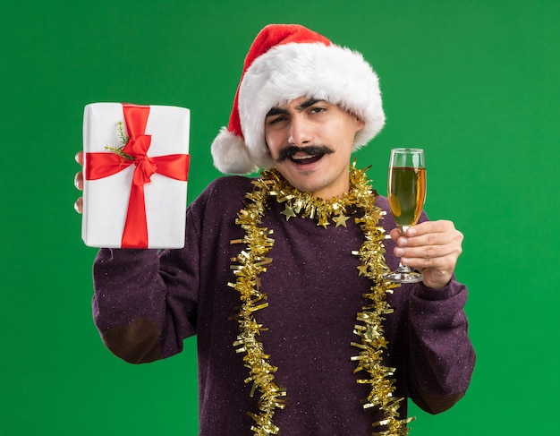 Szczęśliwy młody wąsaty mężczyzna w świątecznej czapce mikołaja z blichtrem na szyi trzymający kieliszek szampana i prezent gwiazdkowy patrząc w kamerę uśmiechnięty wesoło stojąc na zielonym tle
