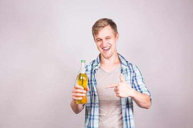 Szczęśliwy młody wesoły mężczyzna trzyma piwo, na szarym tle z miejsca kopiowania.