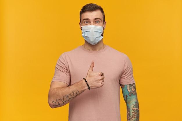 Szczęśliwy młody wytatuowany brodaty mężczyzna w różowej koszulce i higienicznej masce, aby zapobiec infekcji, wygląda pewnie i pokazuje kciuk w górę gestem na żółtej ścianie