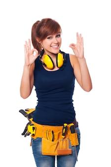 Szczęśliwy młody żeński pracownik budowlany gestykuluje ok znaka