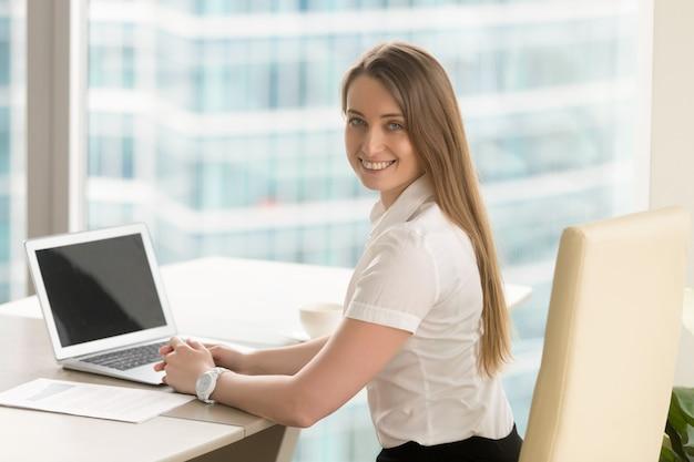 Szczęśliwy młody żeński przedsiębiorca pracuje przy biurem