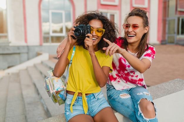 Szczęśliwy młodych dziewcząt przyjaciele uśmiechając się siedząc na ulicy z aparatu fotograficznego, kobiety bawiące się razem