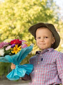 Szczęśliwy młodzieniec trzymający duży bukiet kwiatów zapakowany w prezent dla matki