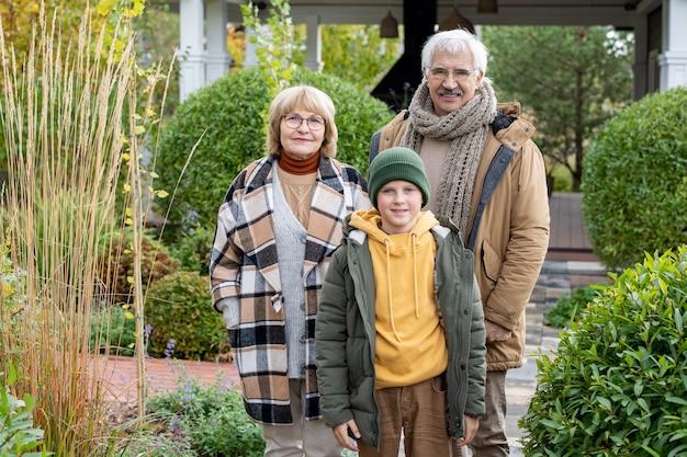 Szczęśliwy młodzieniec w casualwear i jego kochający dziadkowie patrzący na ciebie z uśmiechem stojąc przed kamerą w ogrodzie