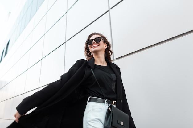 Szczęśliwy model dziewczyna w modzie czarna odzież wierzchnia spacery po ulicy